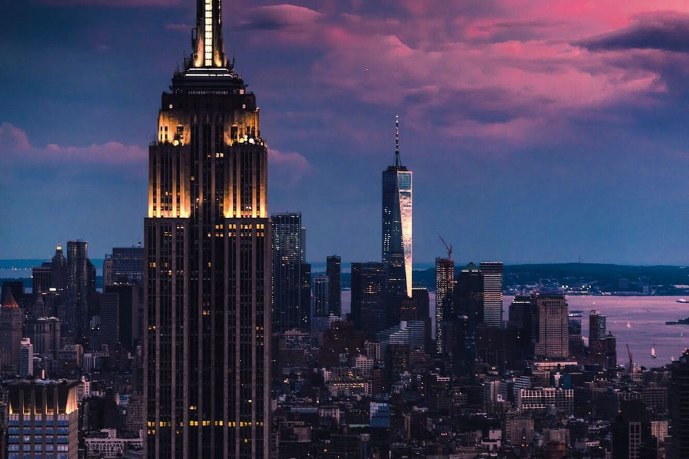 Empire State building surrounded by concrete buildings under cloudy sky
