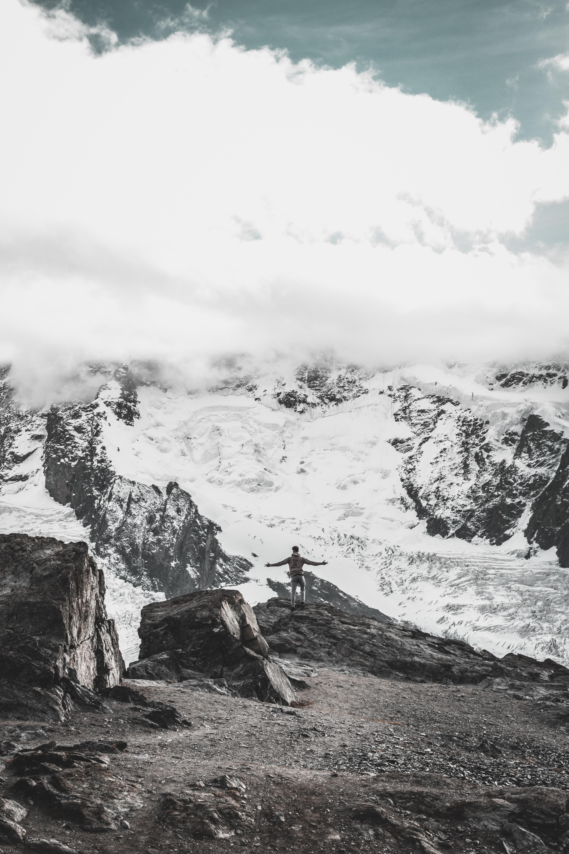 man standing on rock near sea at daytime