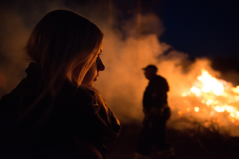 silhouette photography of man and woman nearby bush fire