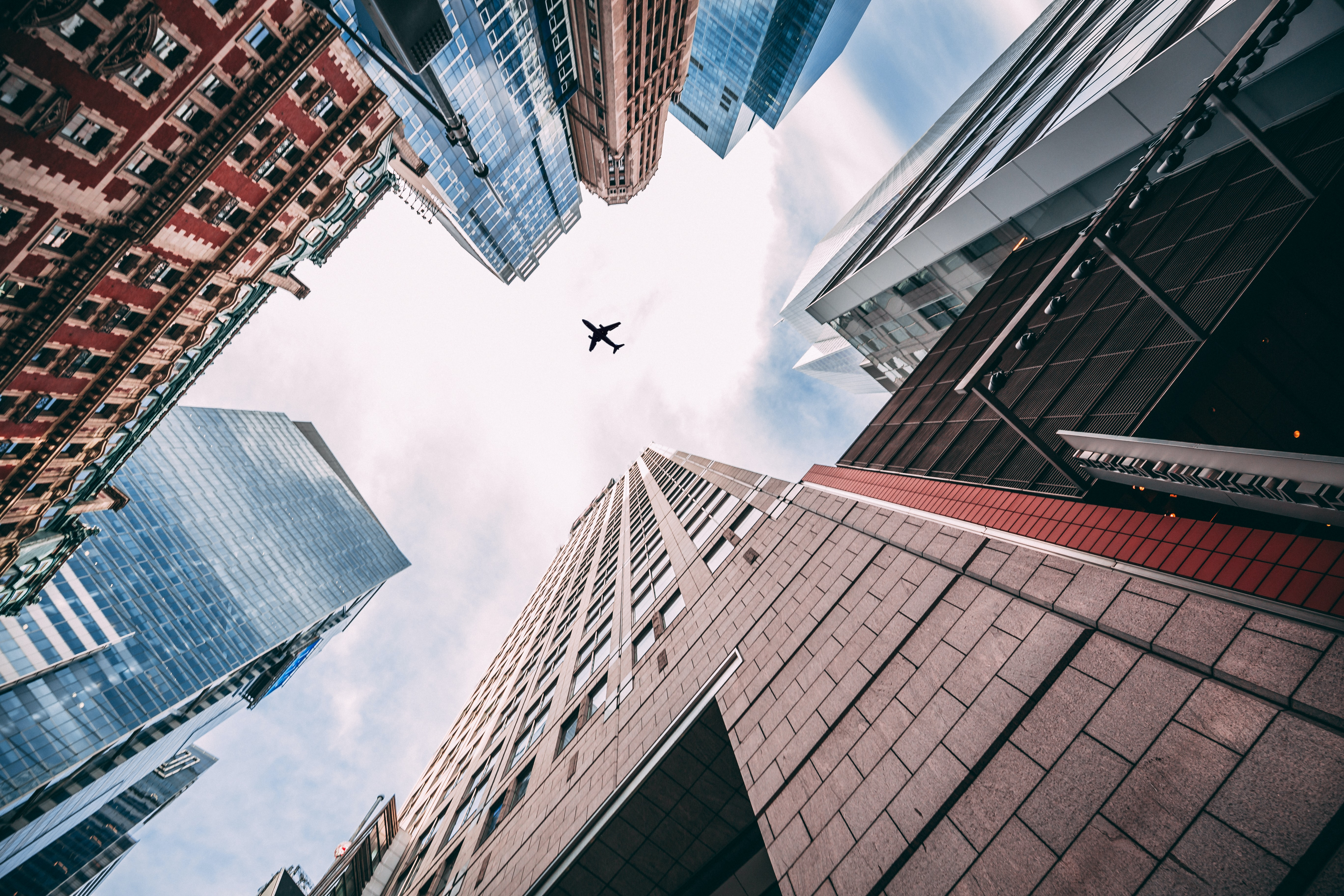 worm's-eye view of an airplane flying above city