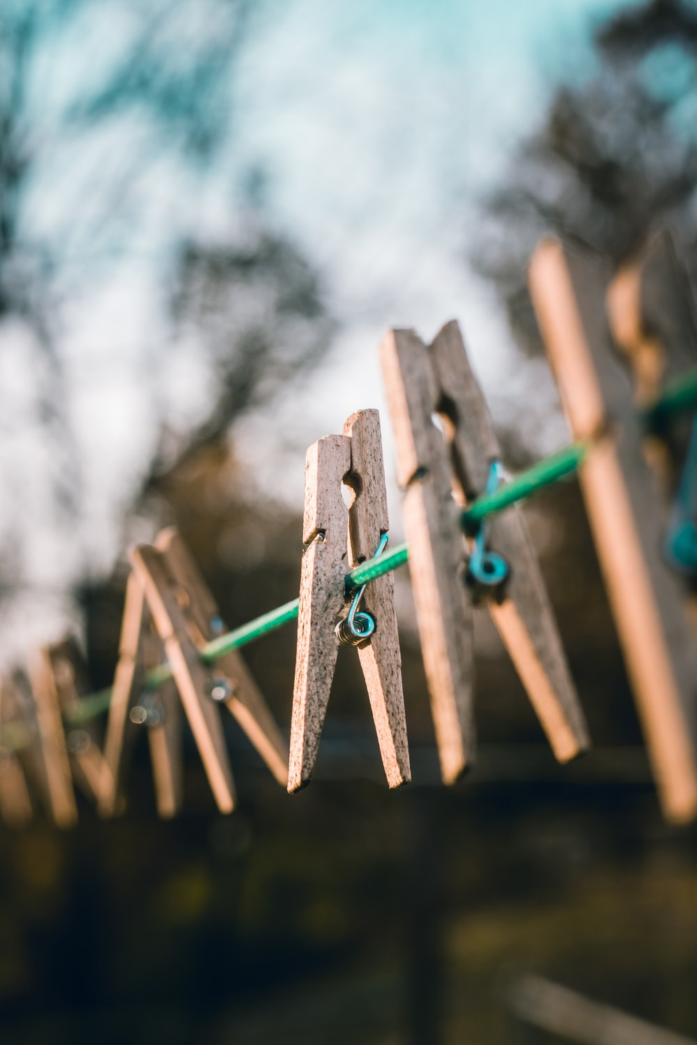selective focus photography of brown clothes clips hanged on green cable outdoor at daytime