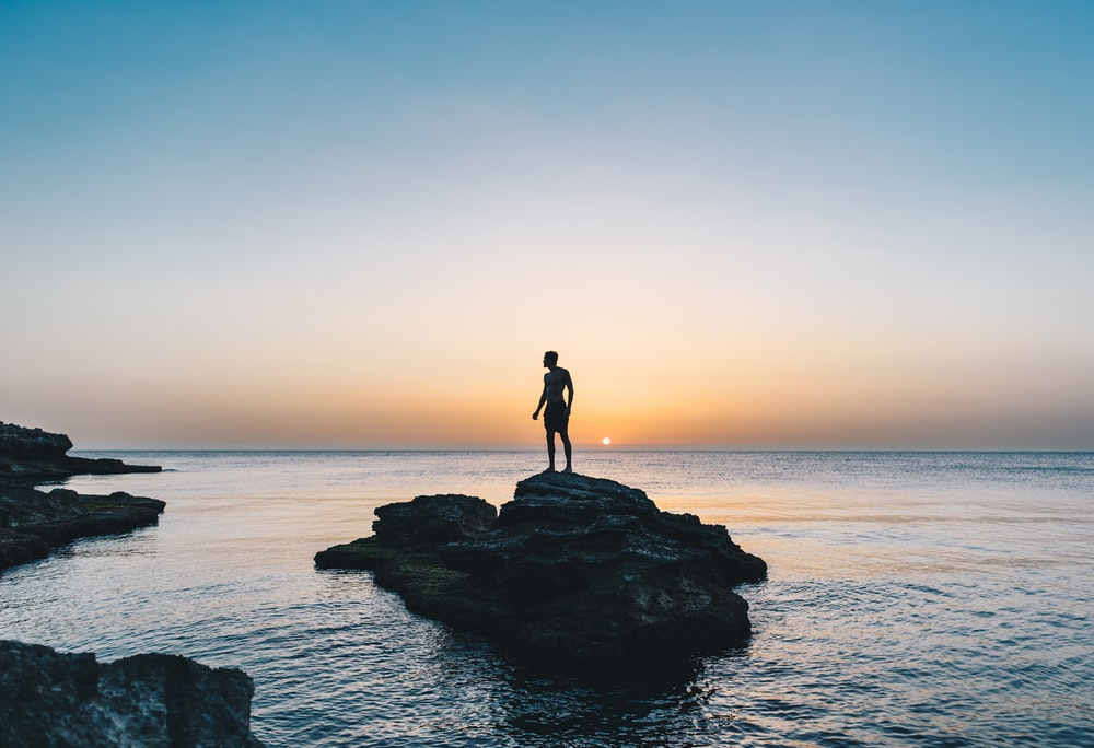 man standing on rock surrounded by body of water