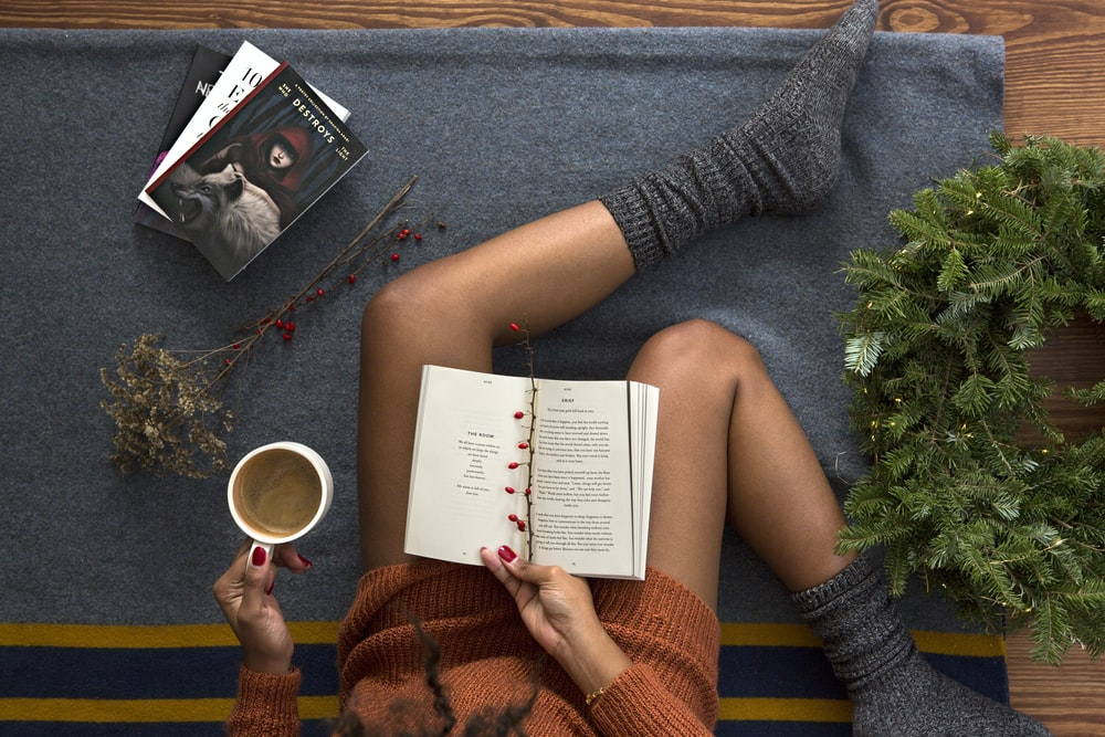 opened book on person's lap with gray socks - christmas-themed novels