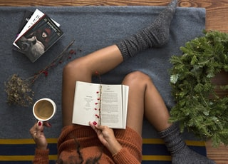 opened book on person's lap with gray socks