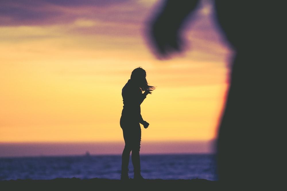 silhouette photography of woman standing at beach