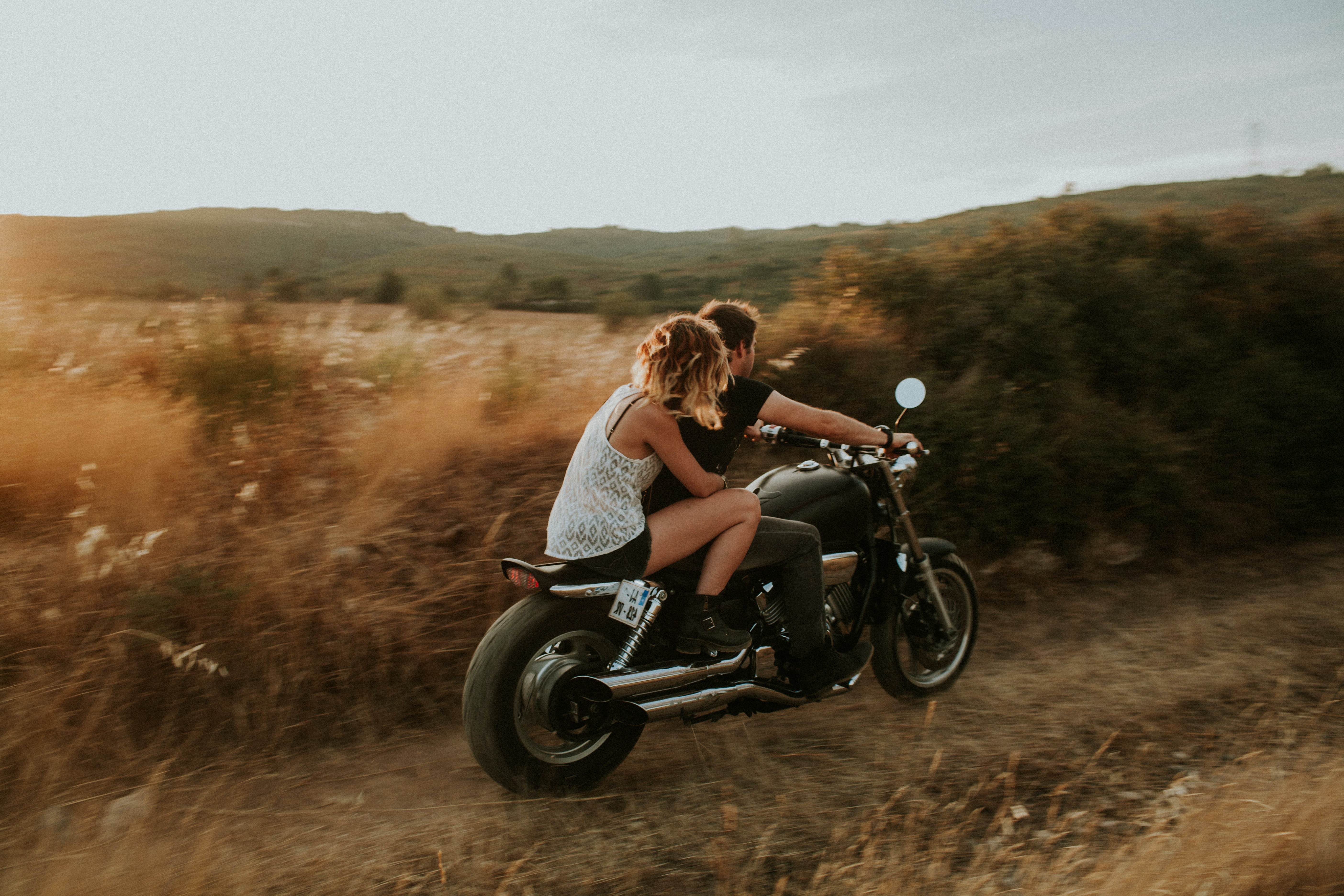 man and woman riding in motorcycle surrounded by brown and green field