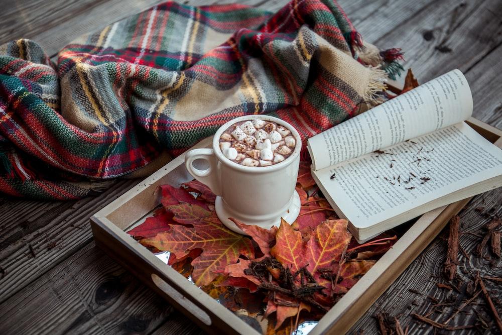 white open book near white ceramic cup