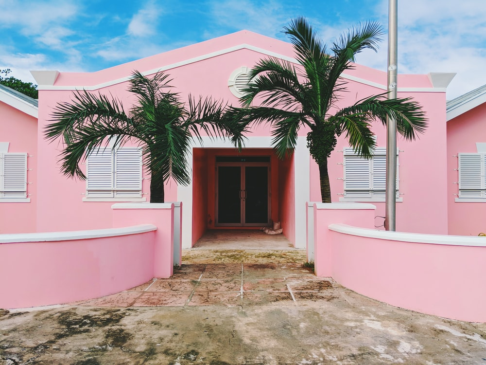 pink and white concrete house near green trees under cloudy sky