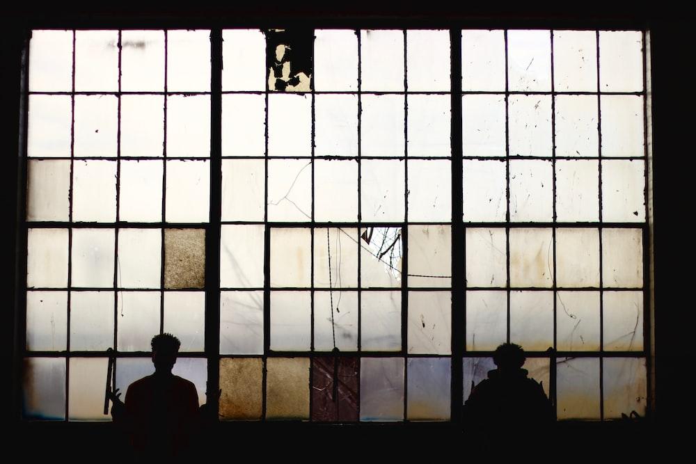 silhouette of people standing near window