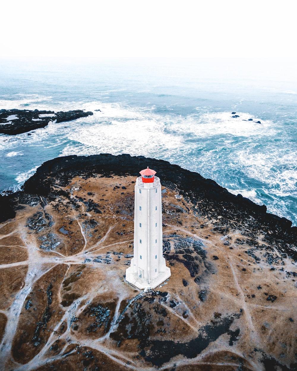 bird's eye photography of white lighthouse tower near ocean
