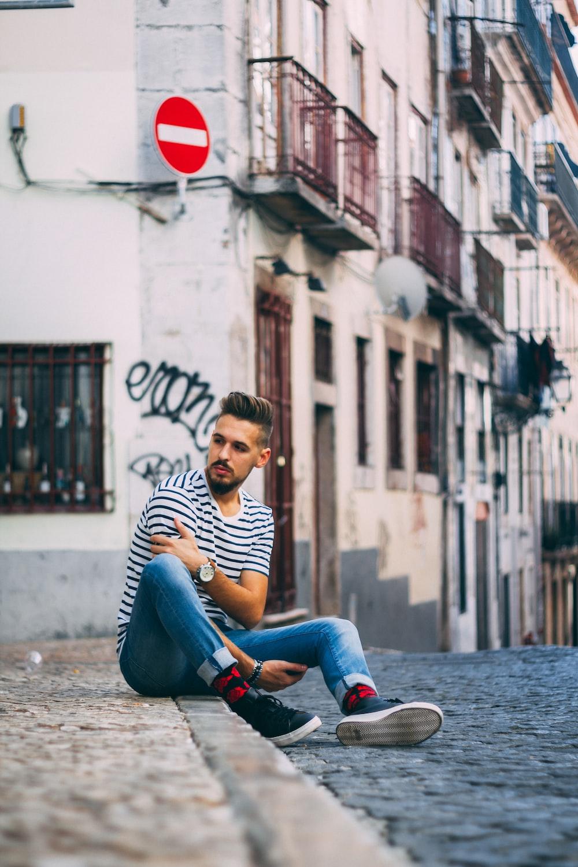 man sitting on road gutter