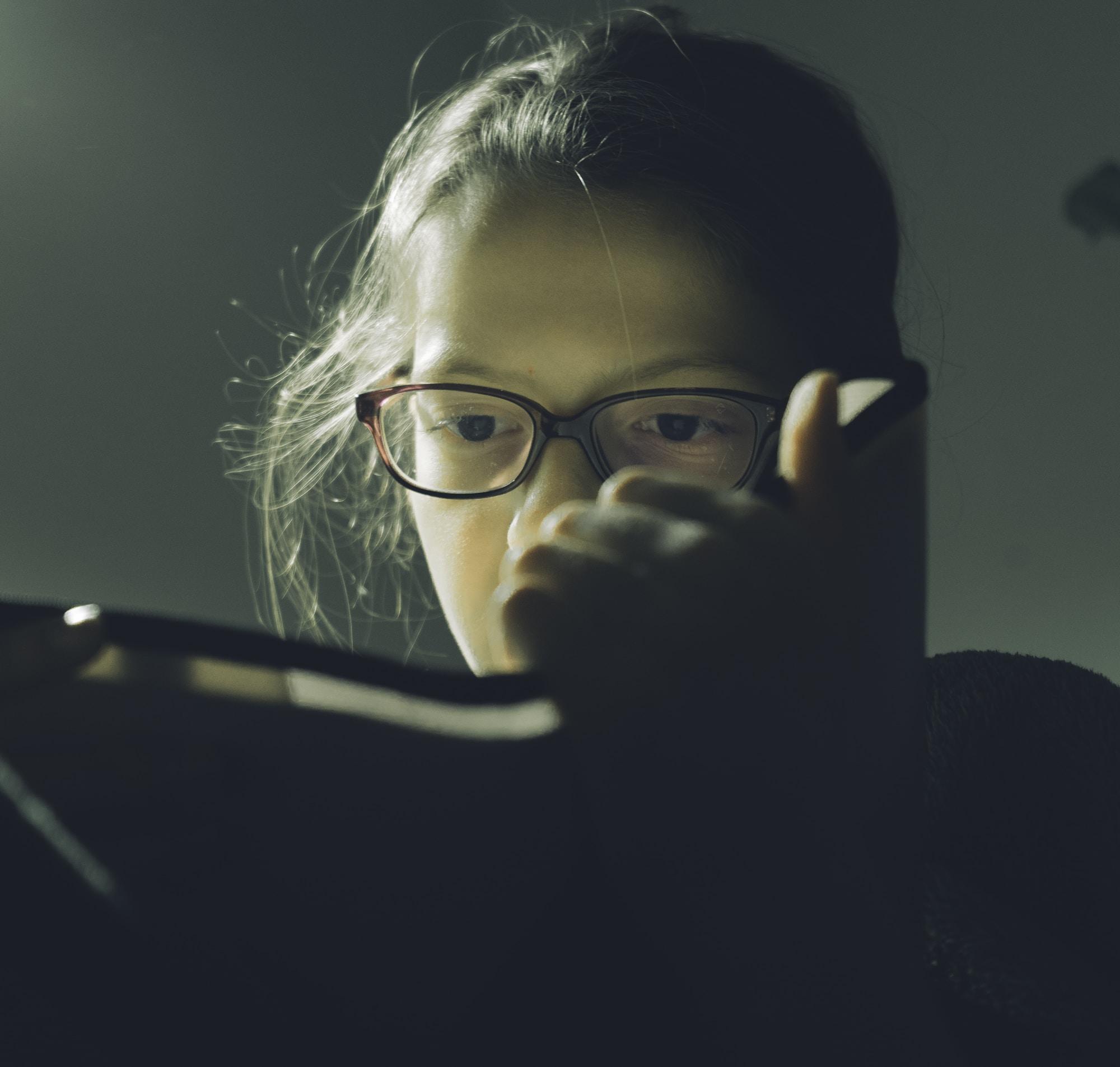 woman wearing eyeglasses reading book