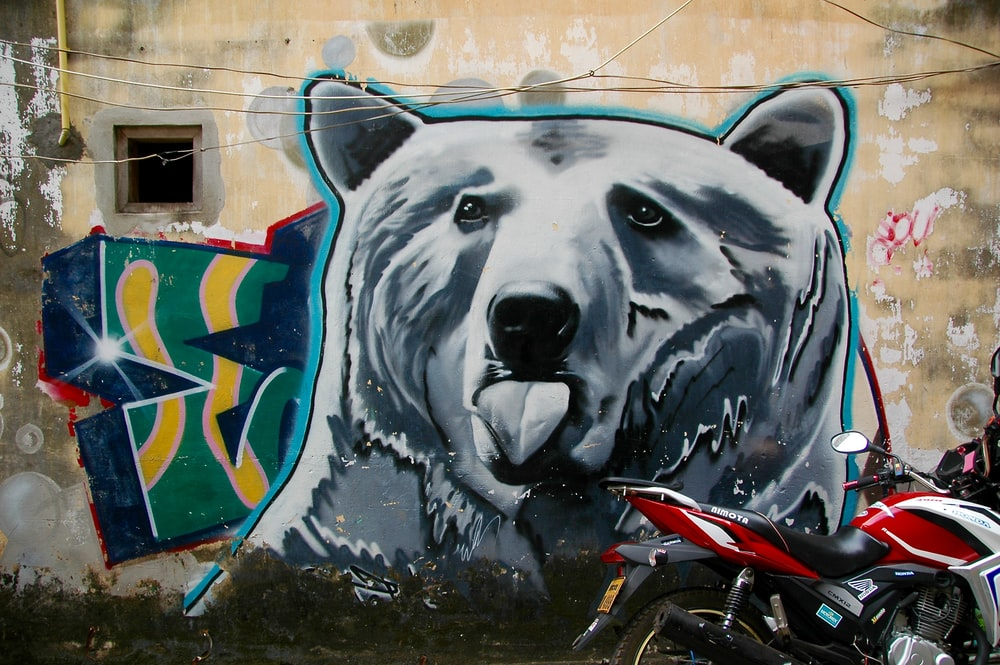 red motorcycle park next to wall with bear painting