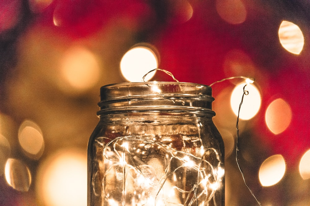 shallow focus photo of clear glass mason jar with string lights