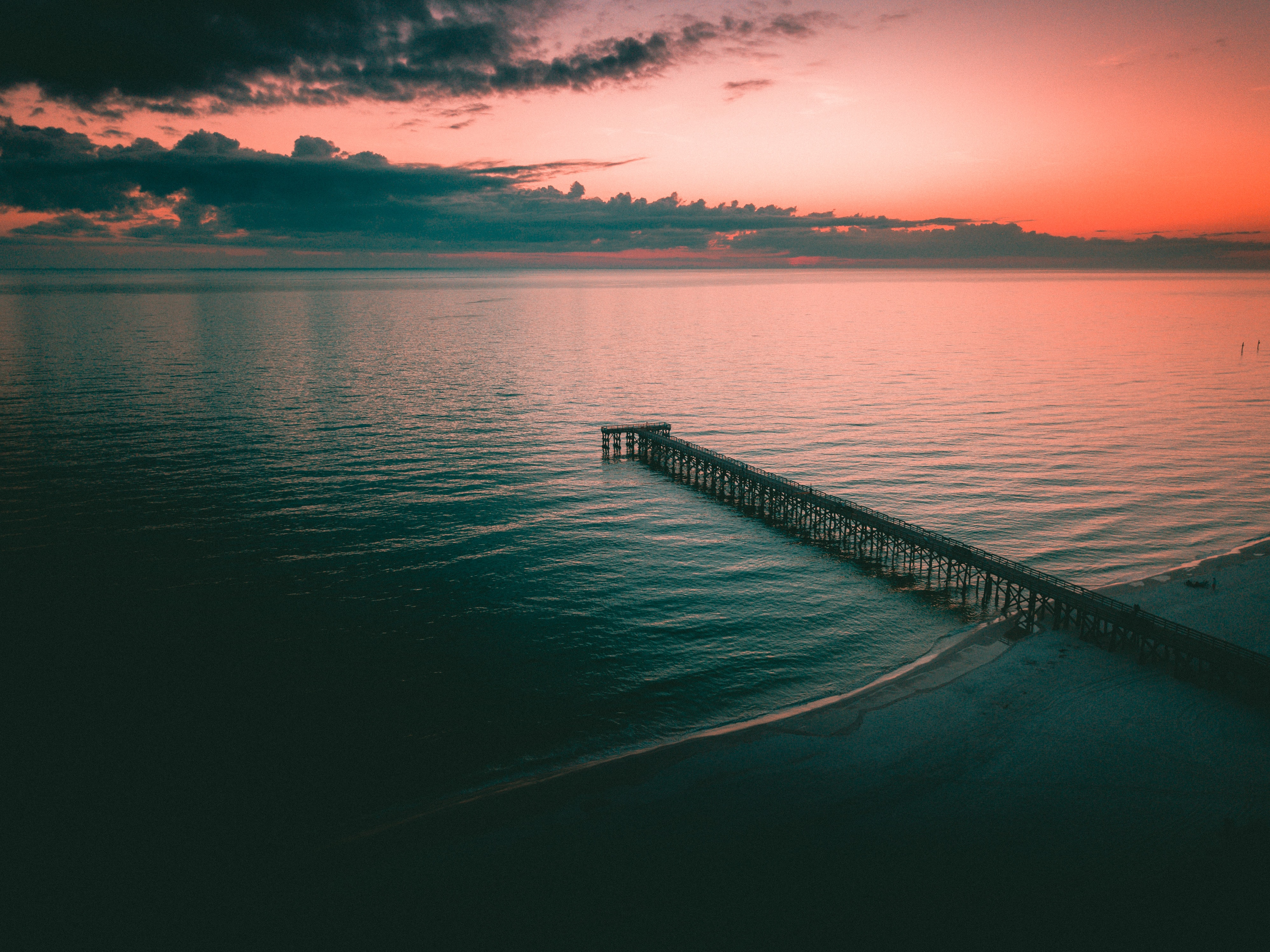 black metal dock on calm water under golden hour