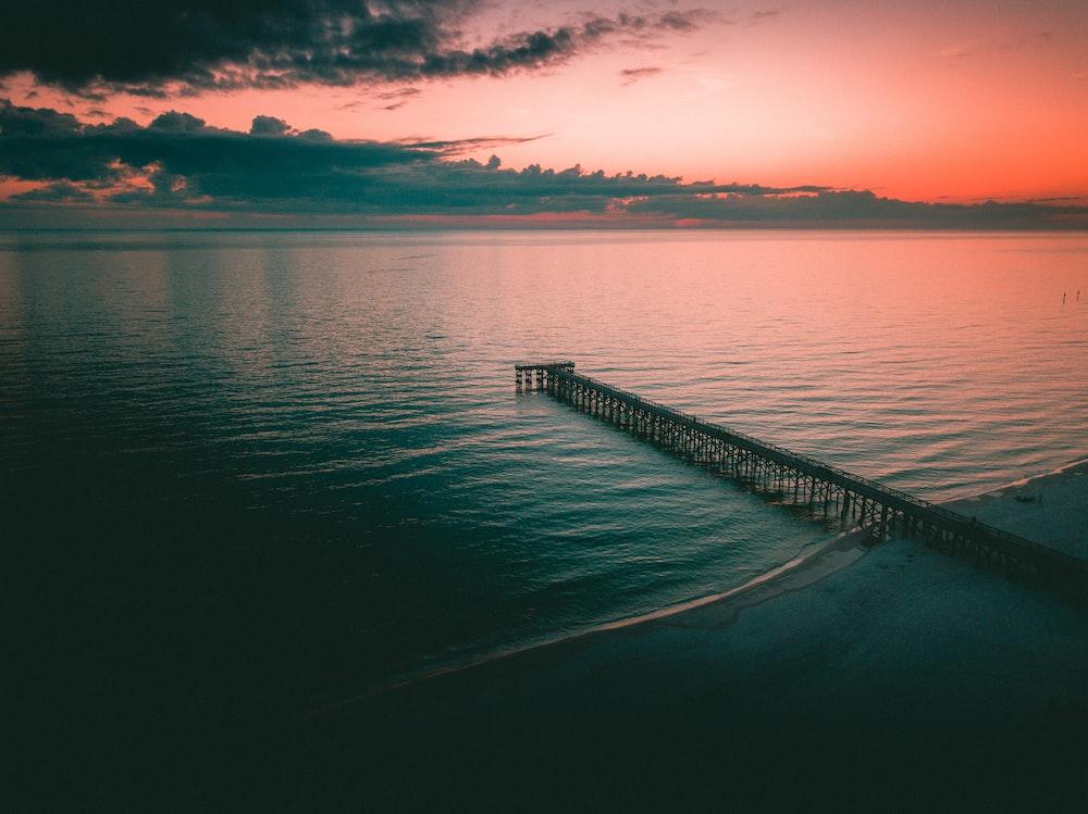 black metal dock on calm water under golden hour