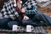 two person cuddling on gray plaid mat