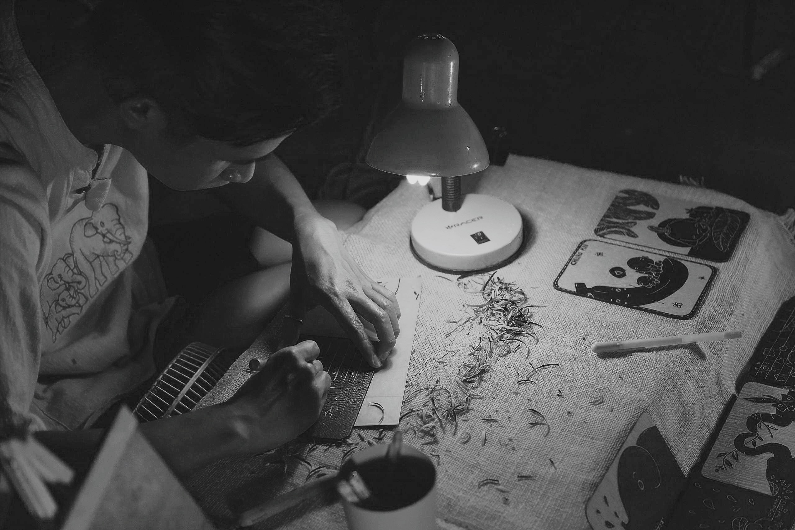 grayscale photography of man writing on brown paper near turned on lamp