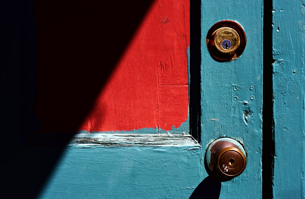 closed teal wooden door with brass-colored door knob