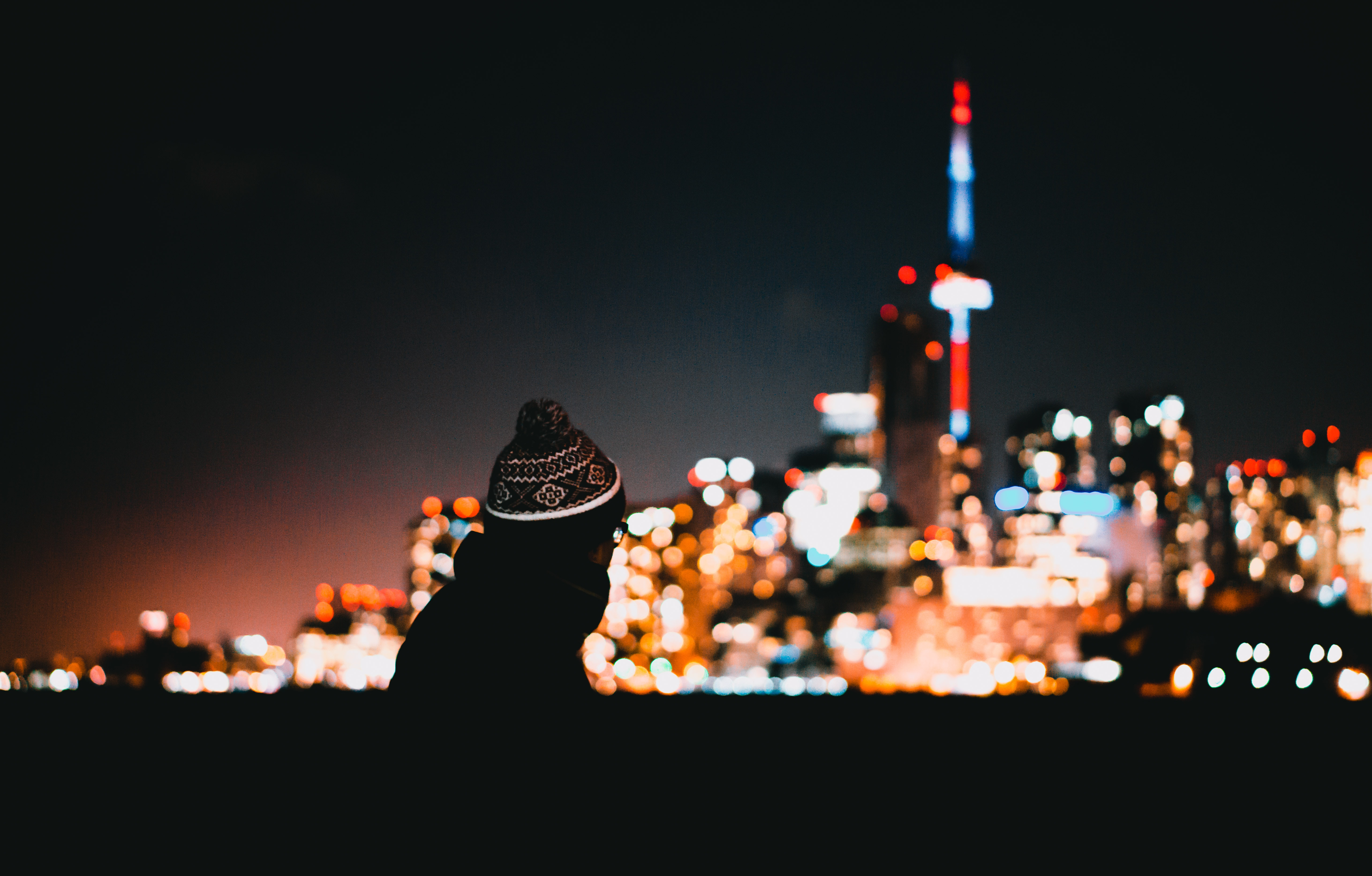 person wears hat beside building on bokeh photography