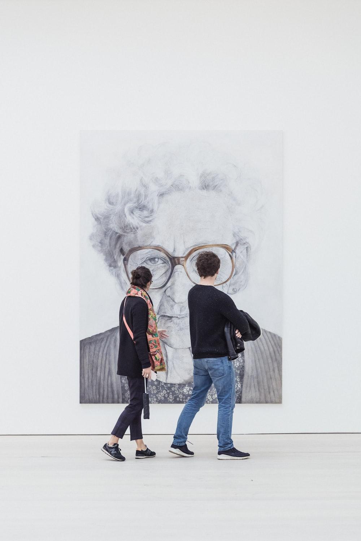 man and woman looking at woman's painting
