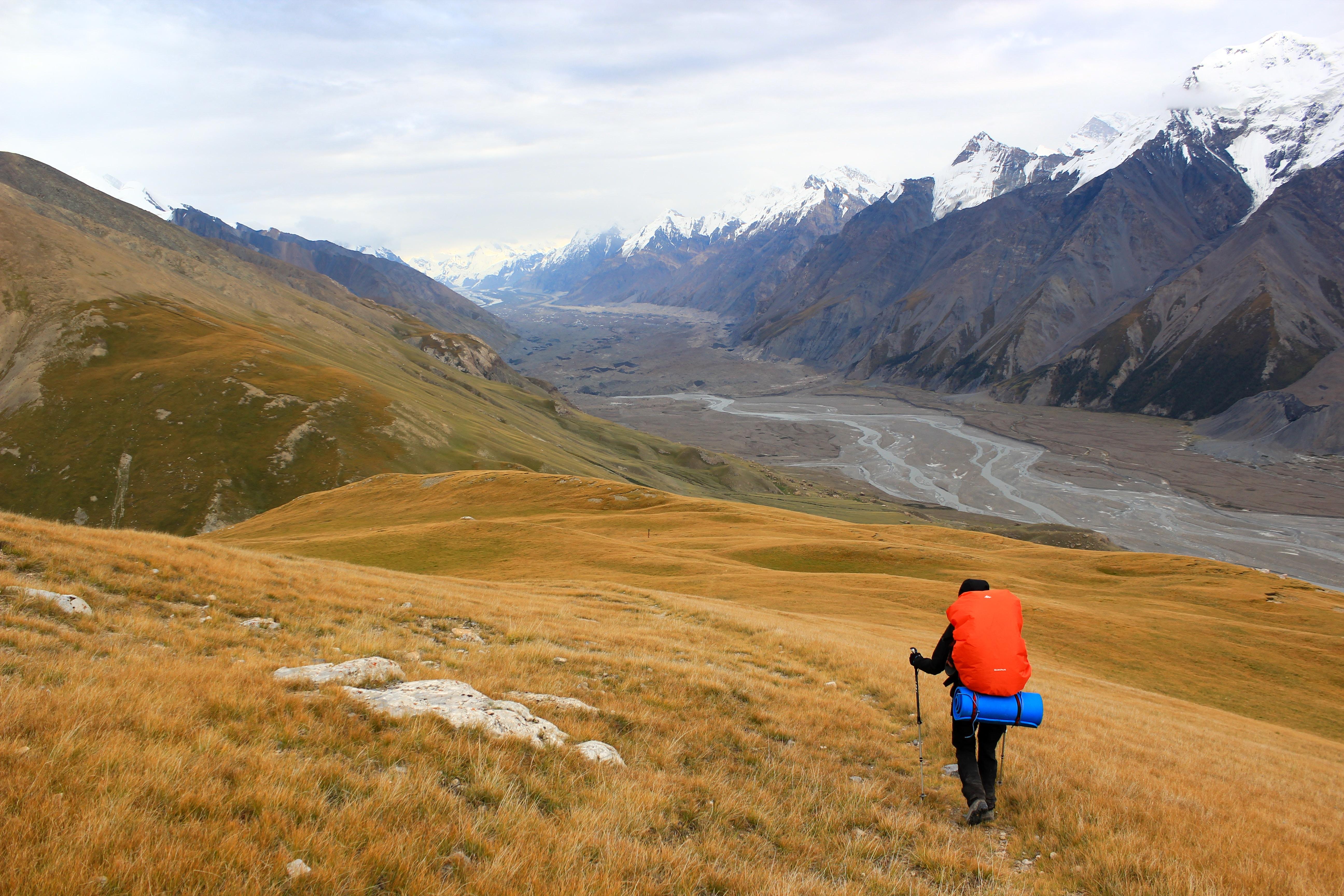man with hiking bag climbing on mountains