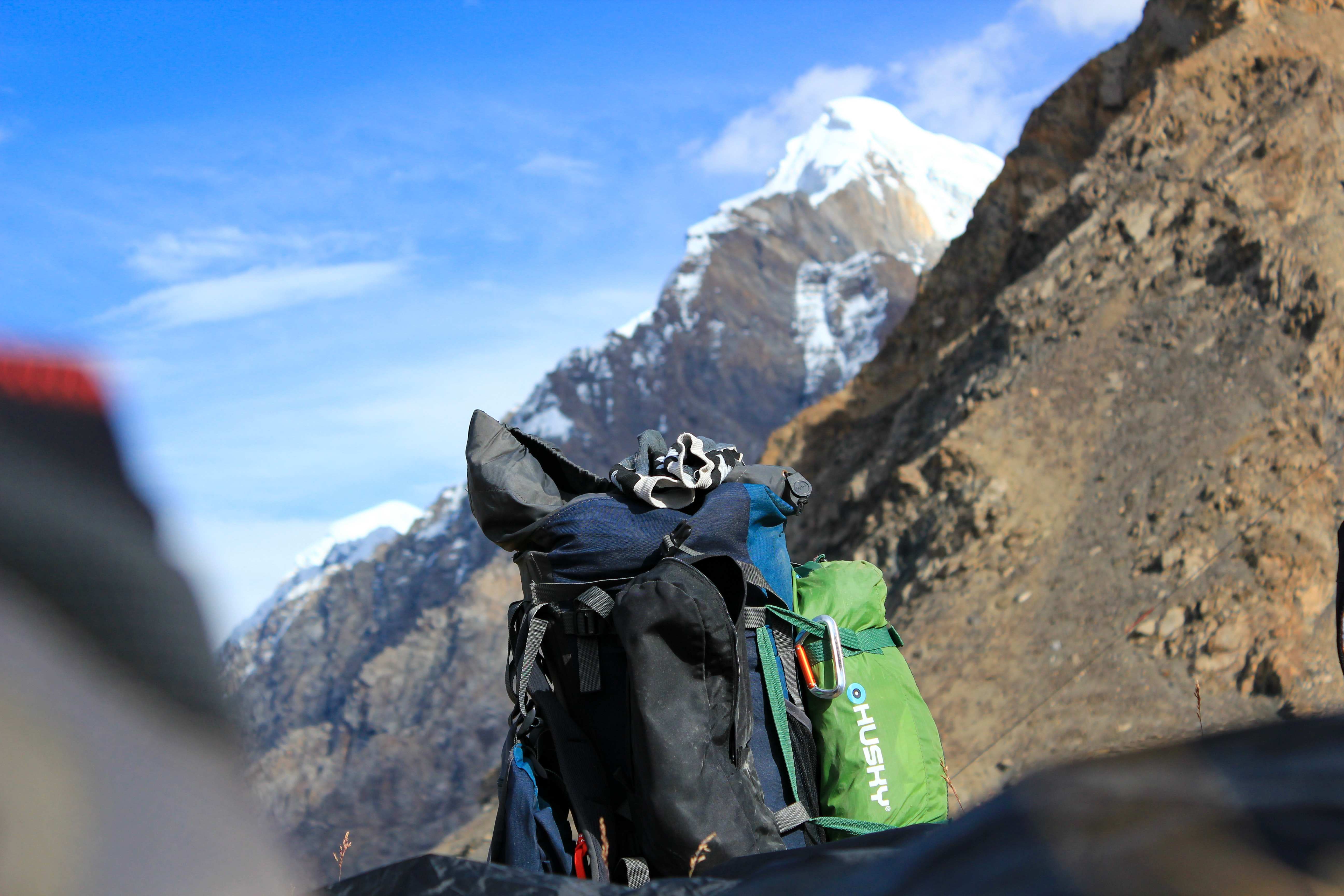 black and green travel backpack near mountain at daytime
