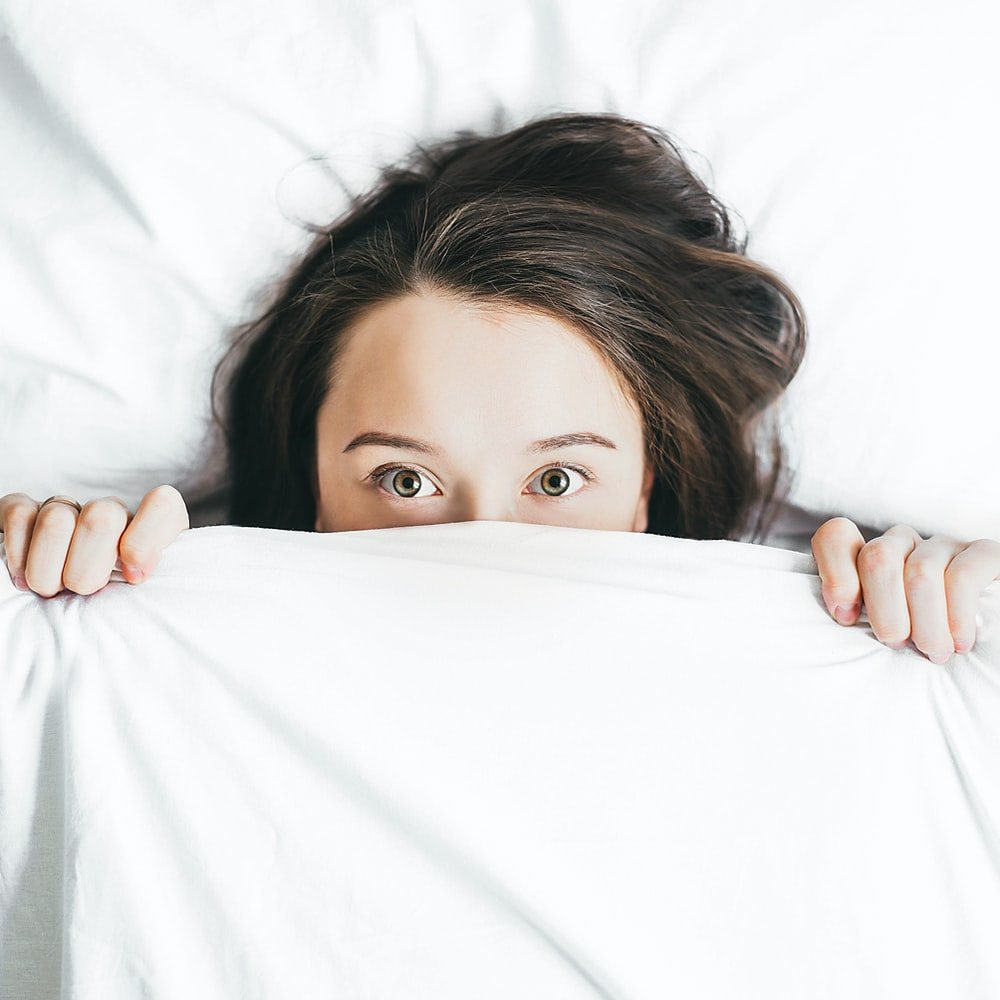 woman covering her face with blanket