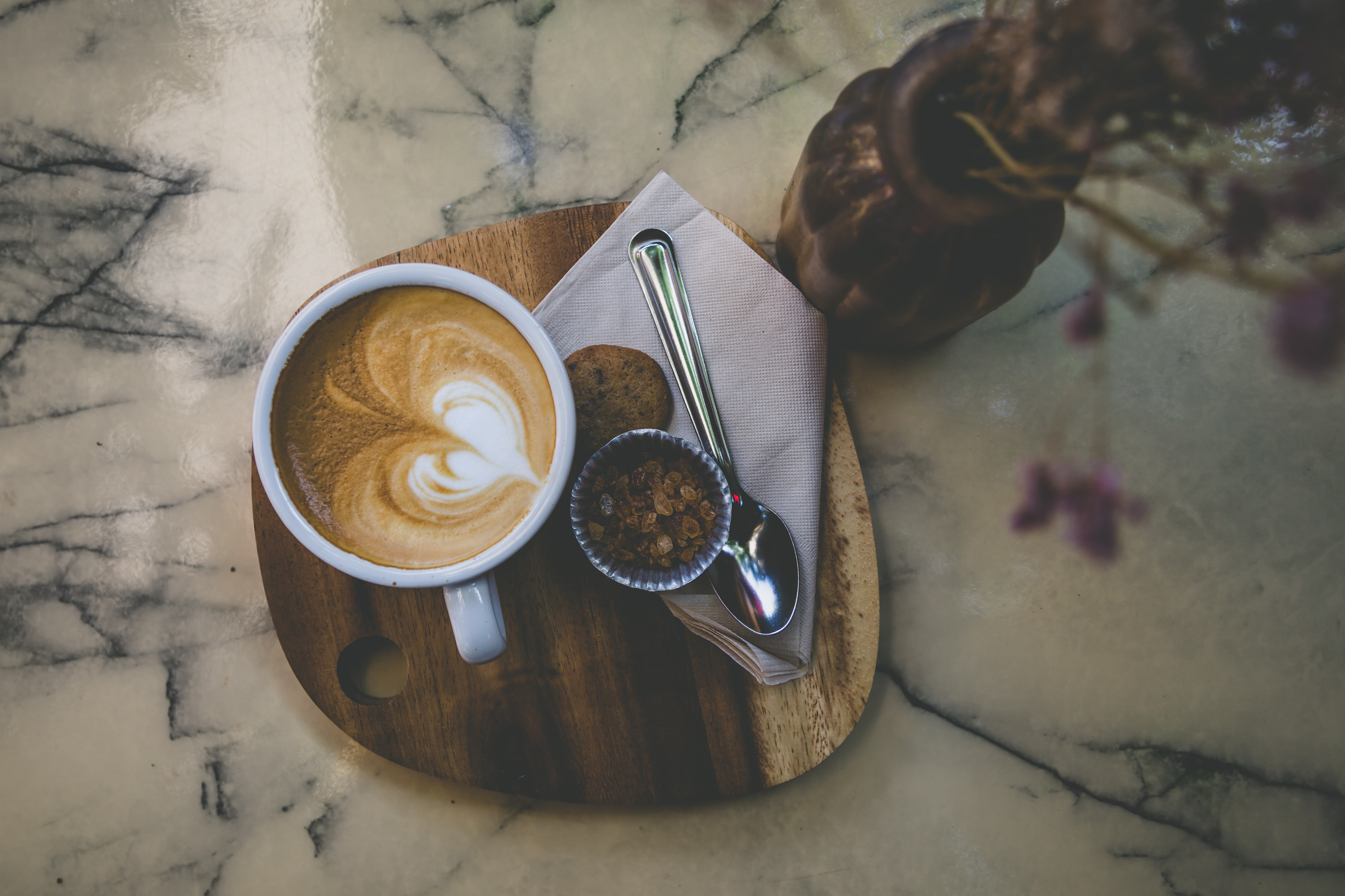 spoon near coffee cup and brown vase