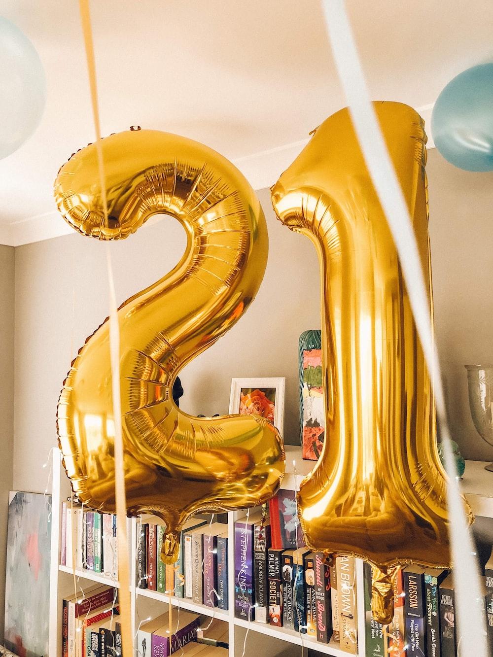 brass-colored 21 foil balloons inside room