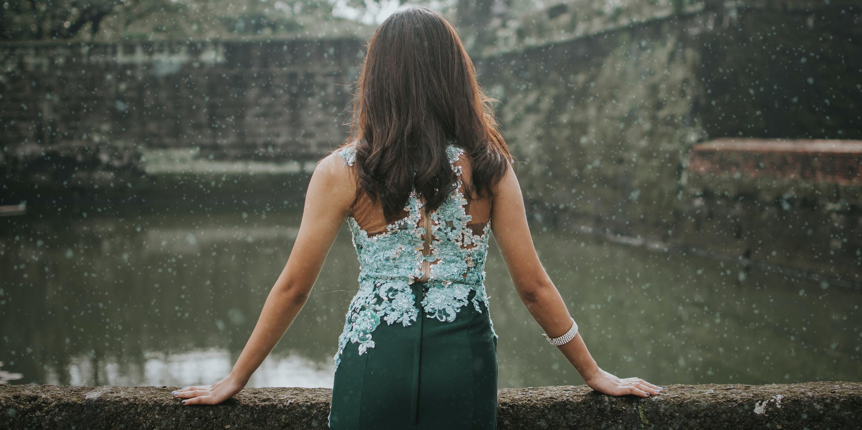 woman standing near wall facing body of water