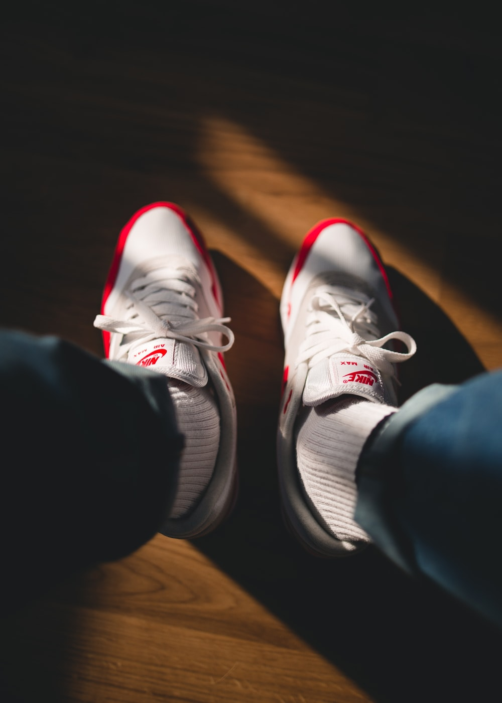 person holding white-and-red Nike running shoes