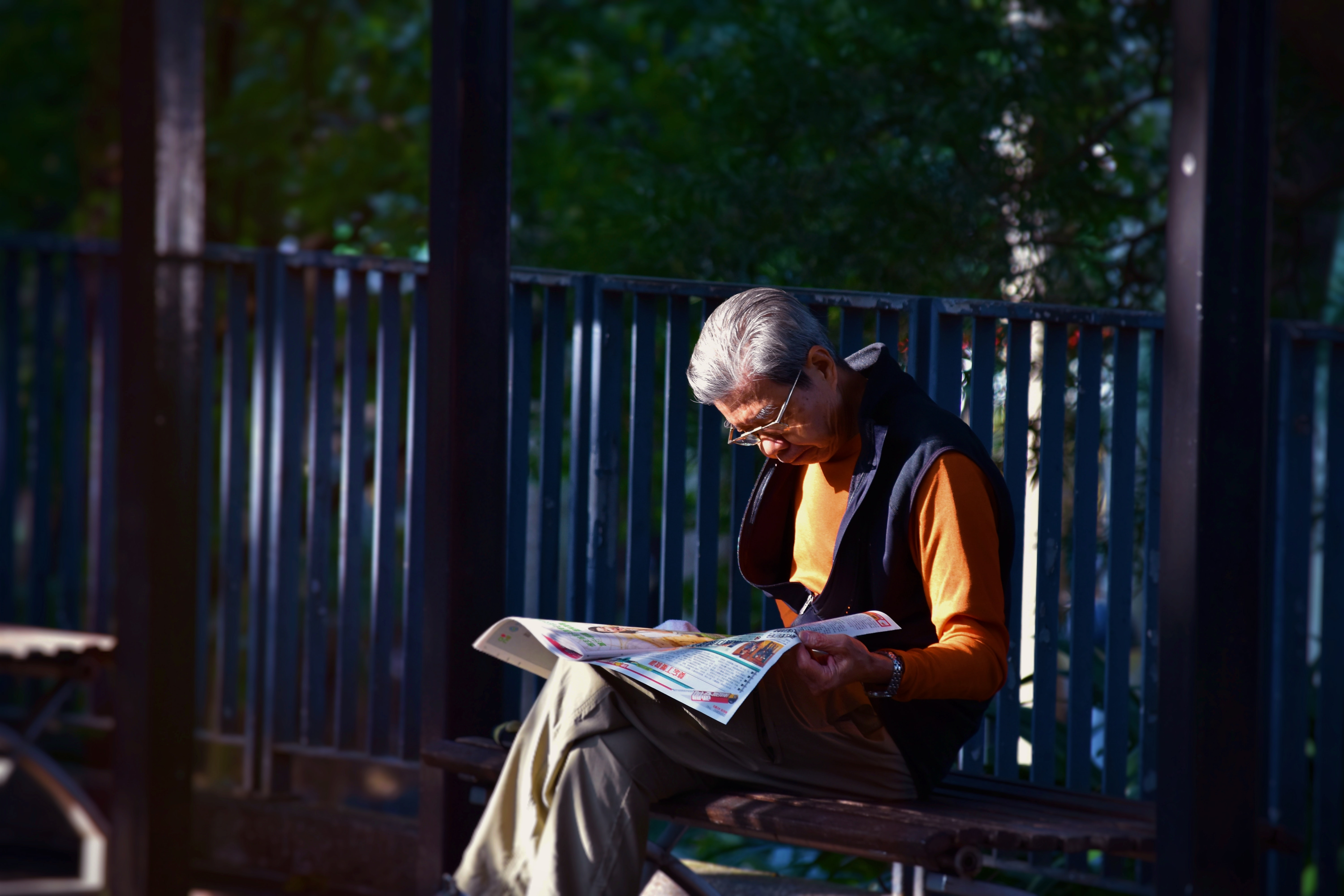 man reading newspaper while sitting on bench in front of wooden fence