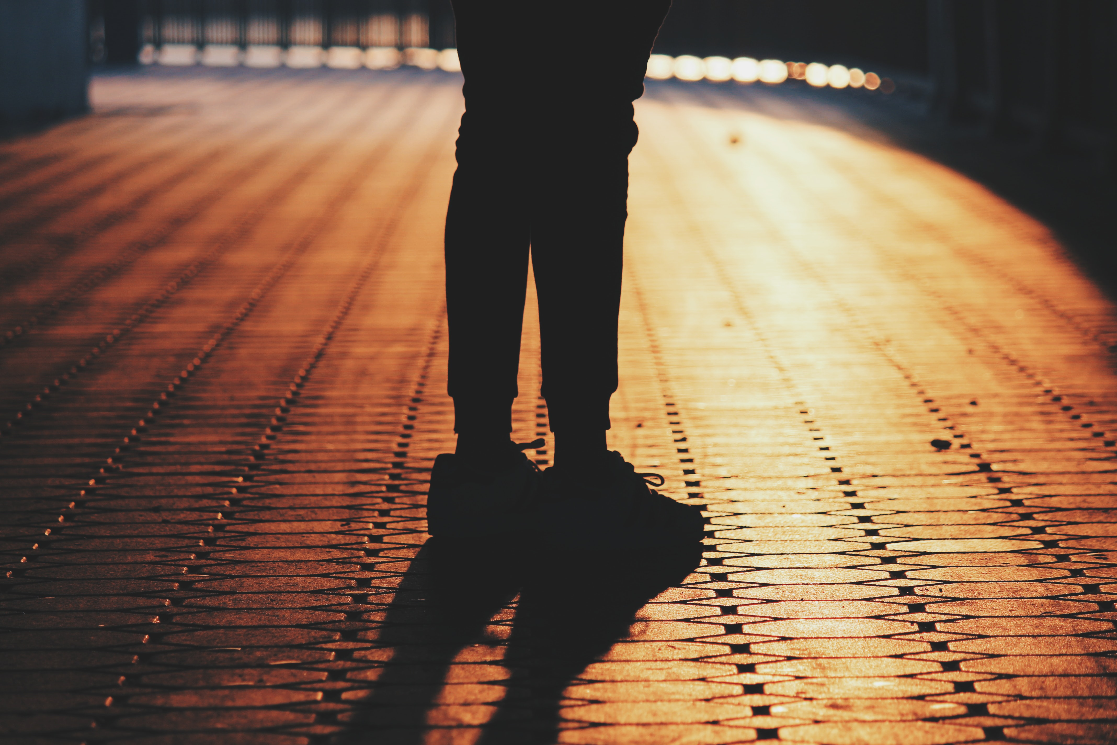 silhouette of man standing on concrete pavement