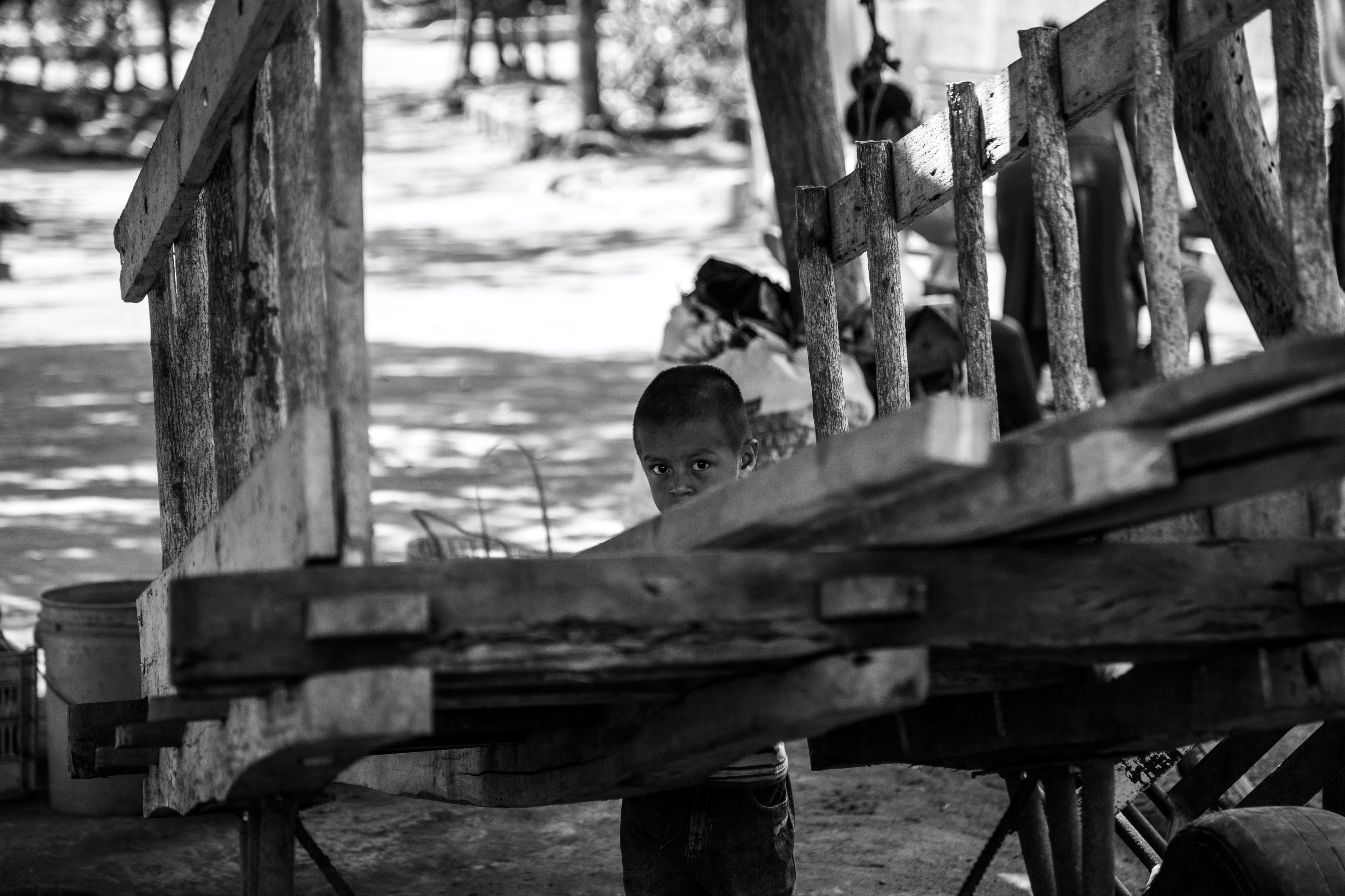grayscale photography of child standing behind trailer