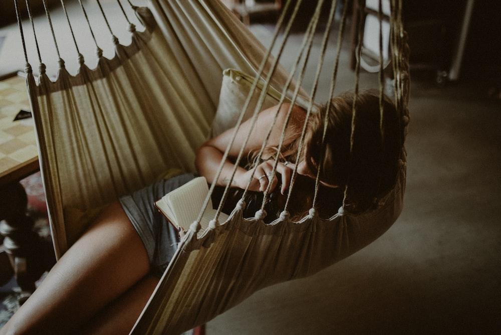 woman reading book on beige hammock