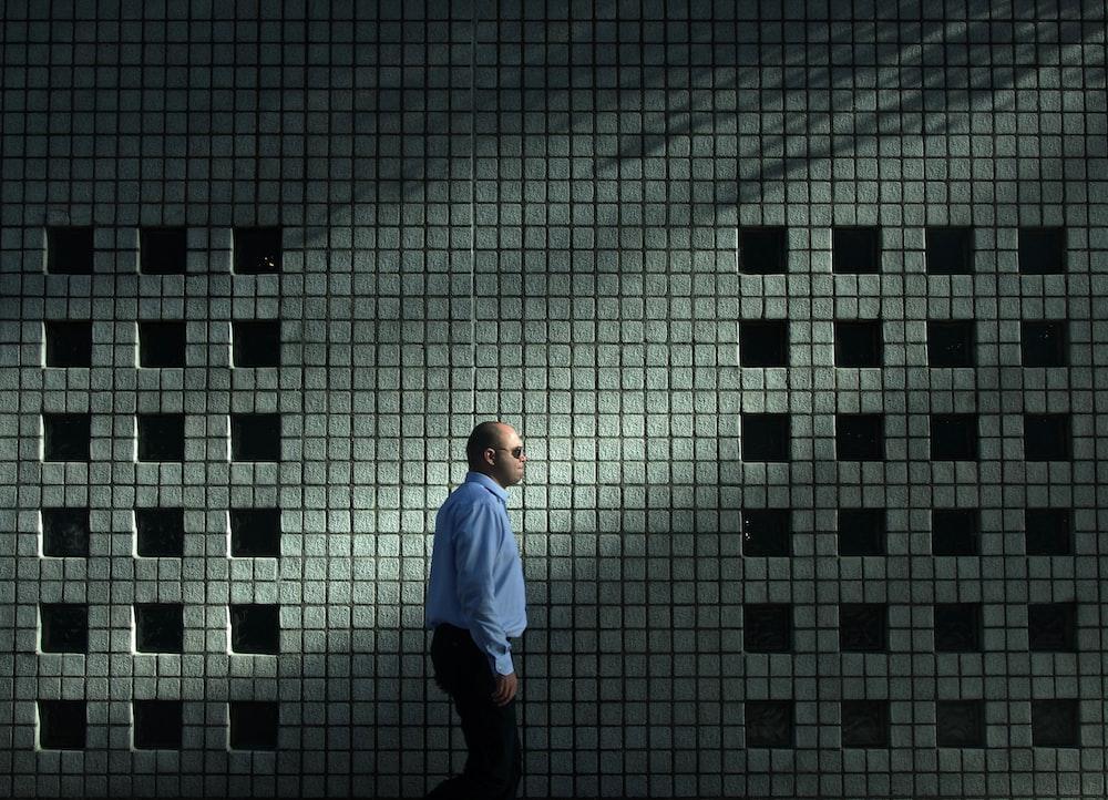 man in blue dress shirt walking near gray concrete wall