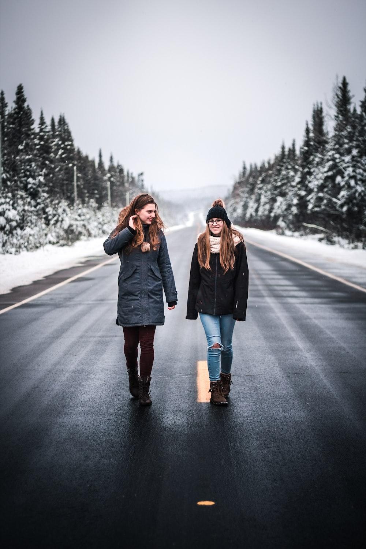 two women walking on gray road between trees