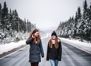 two women walking on gray road between trees