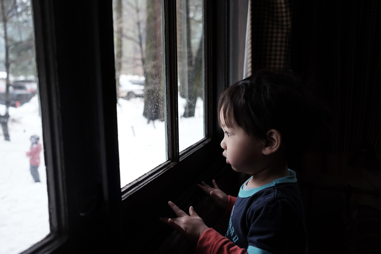toddler boy standing near window during daytime