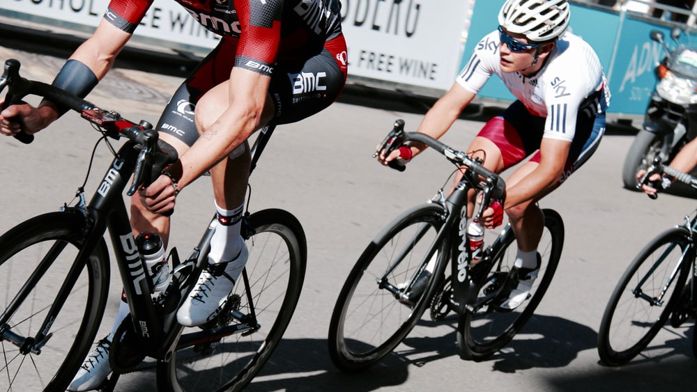 three men racing bicycles