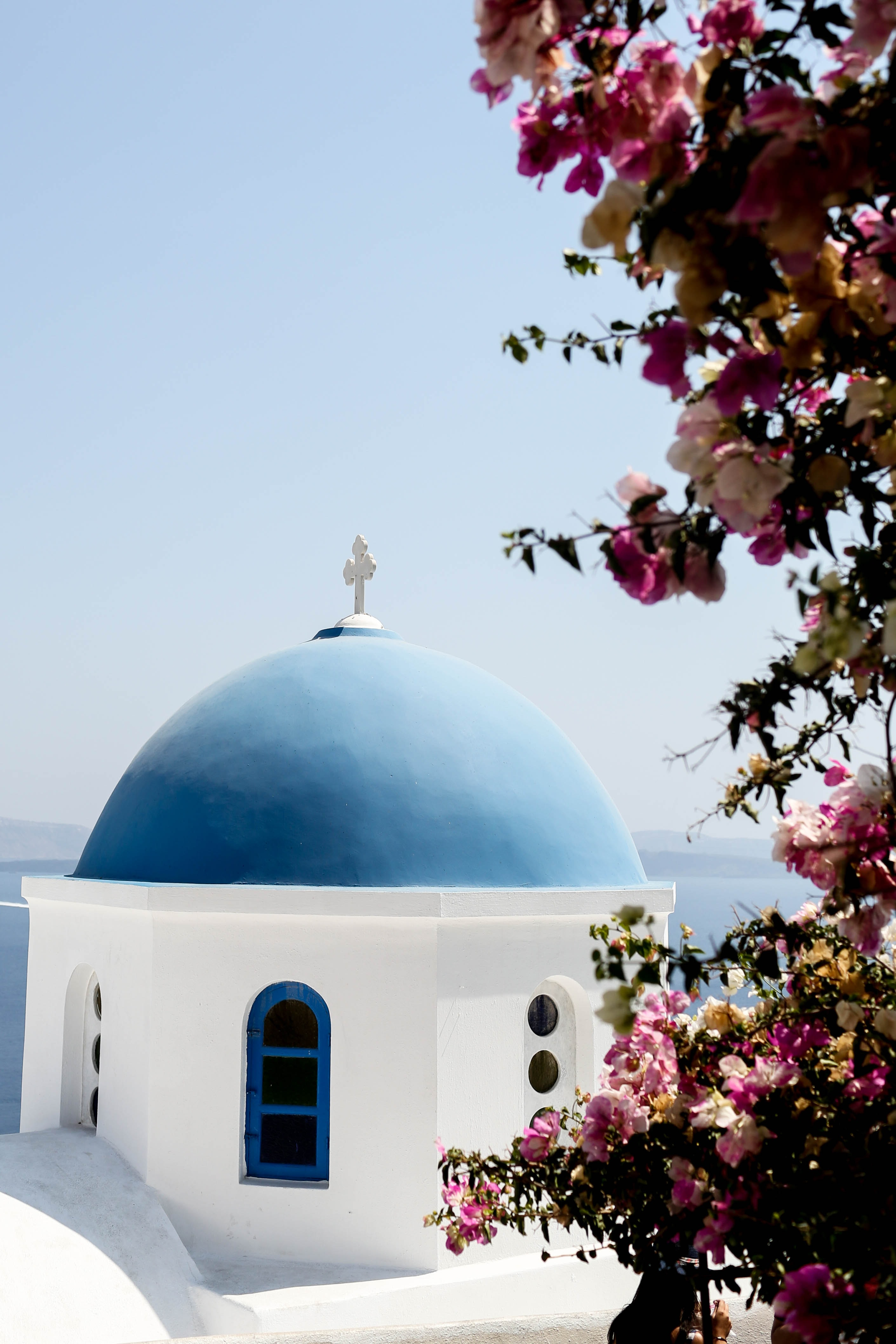 Blue roofed dome with bougainvillea against the sea
