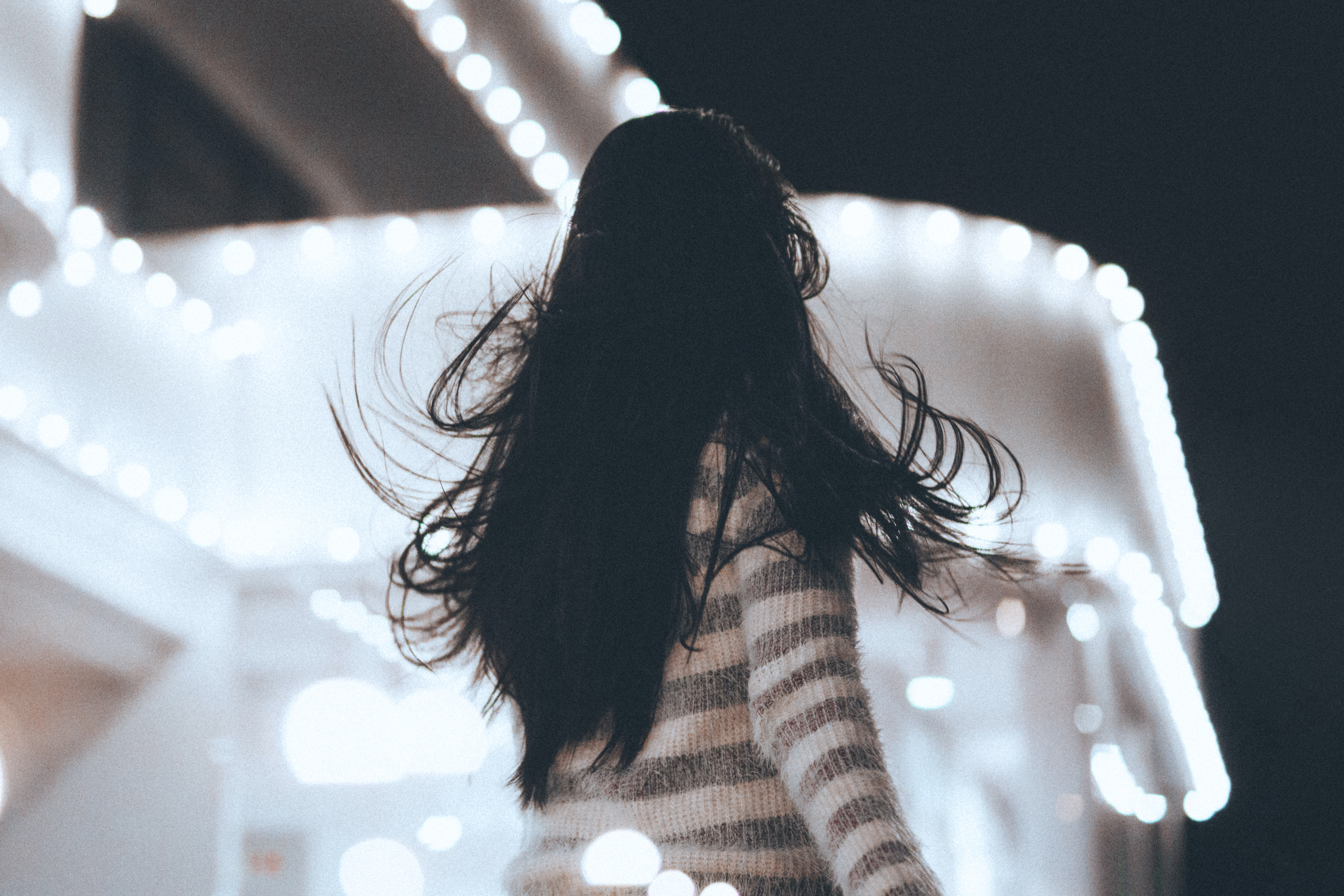 shallow focus photography of woman facing white concrete structure during nighttime