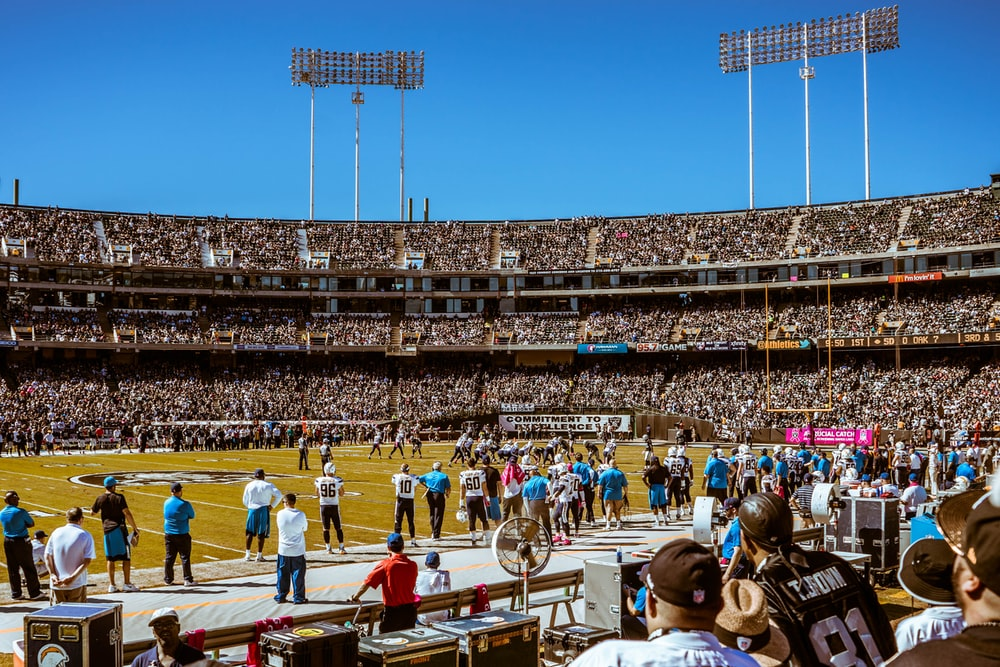 group of people watching football game during daytime