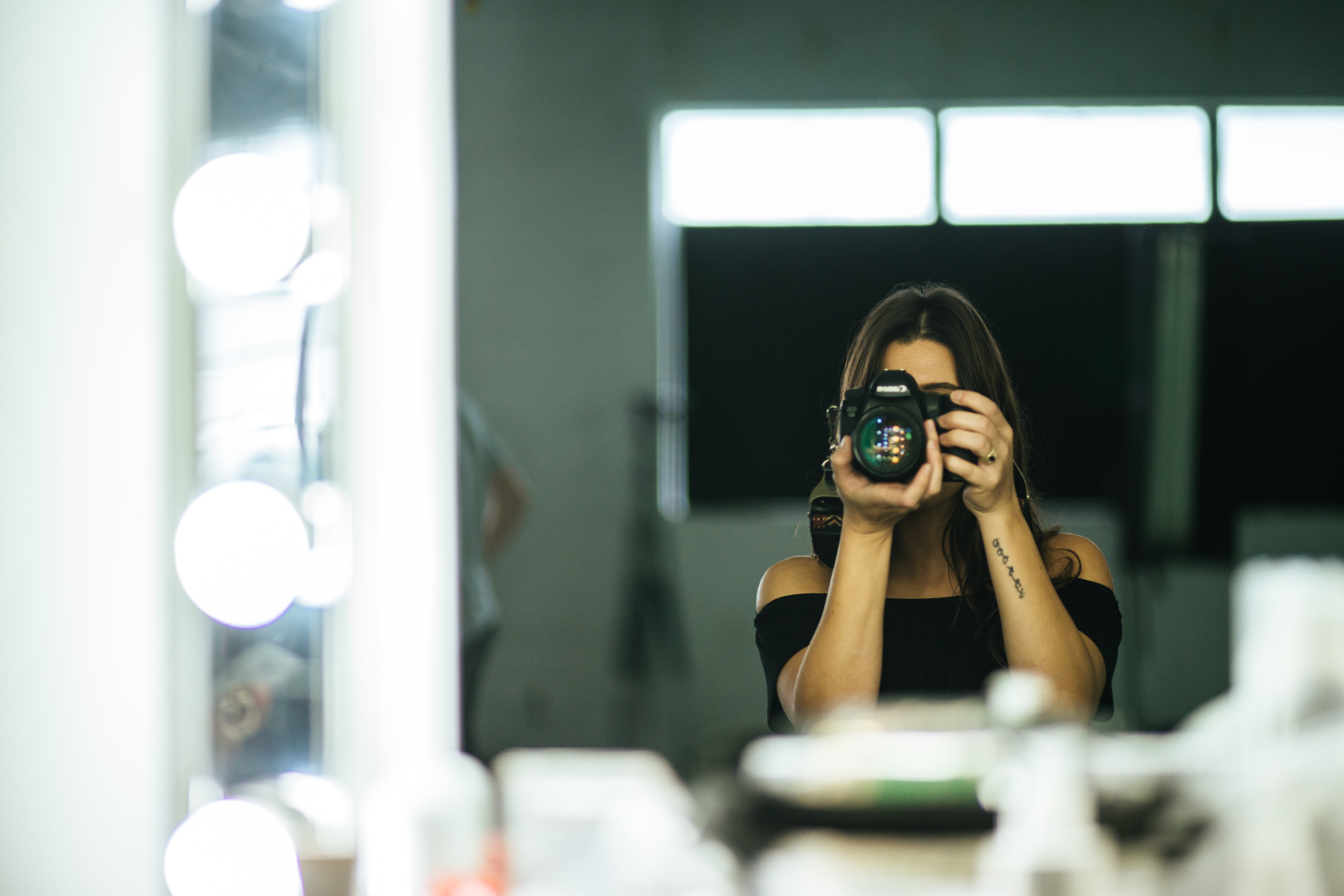woman taking photo of herself in the mirror