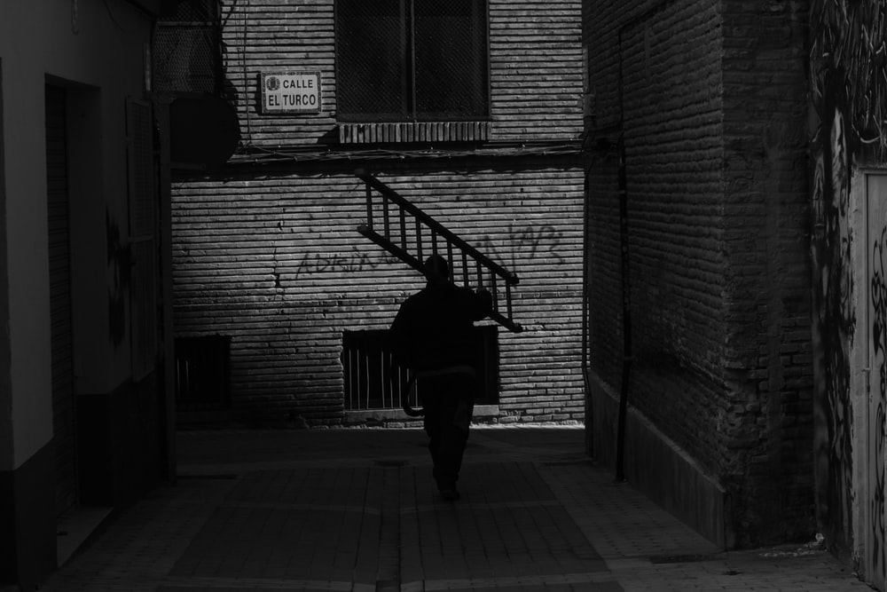 grayscale photography of man carrying ladder