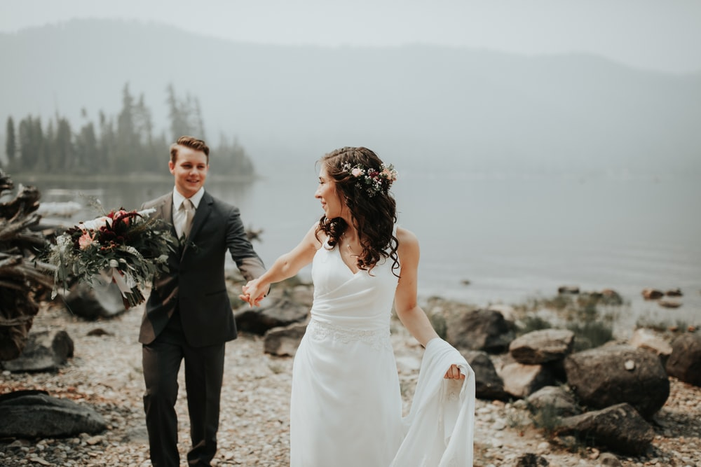 bride and groom standing near body of water