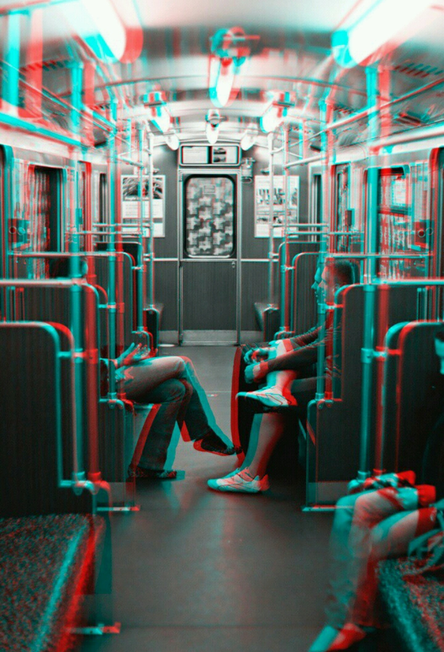 grayscale photo of two person facing each other while sitting inside train