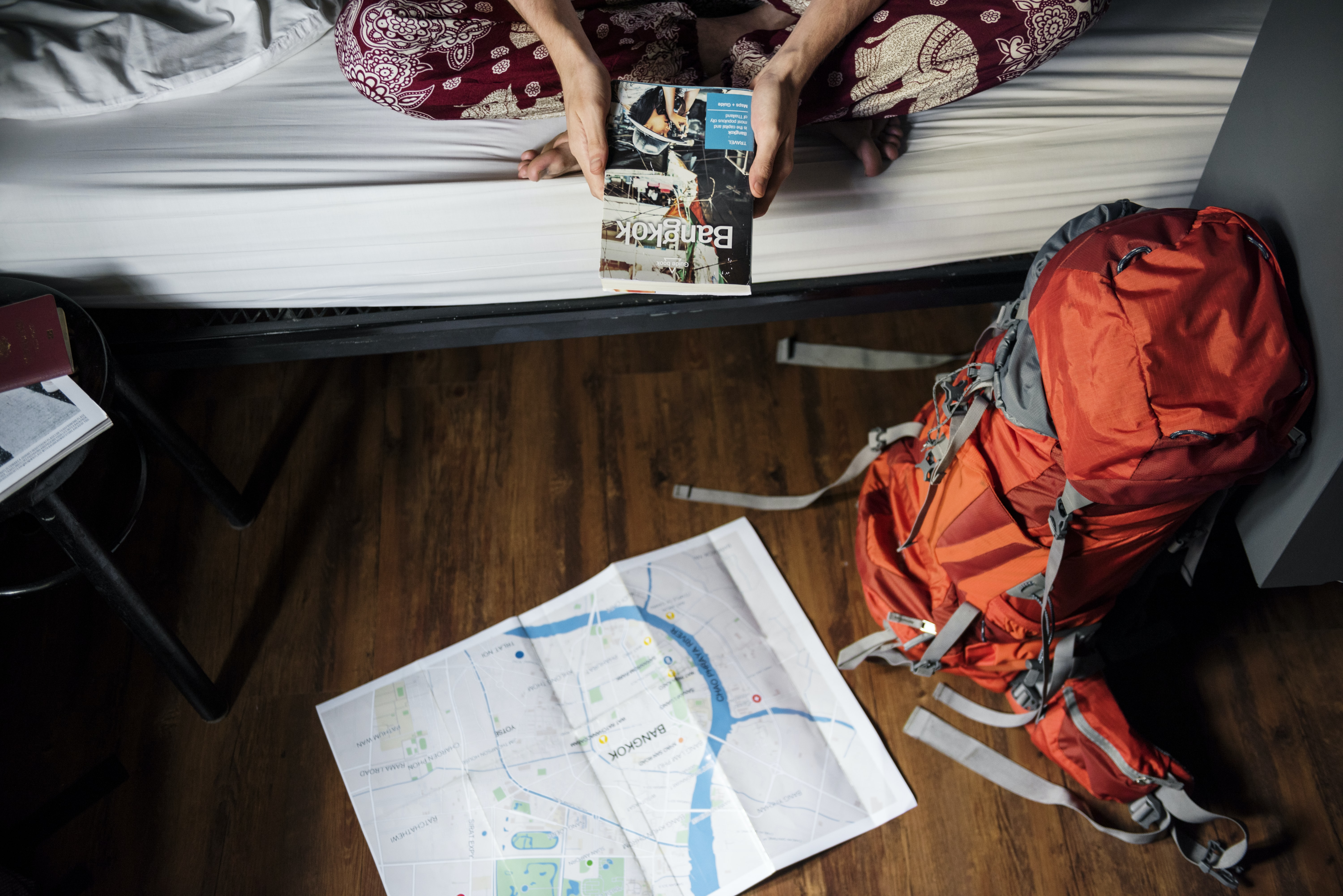 red and grey hiking backpack beside bed