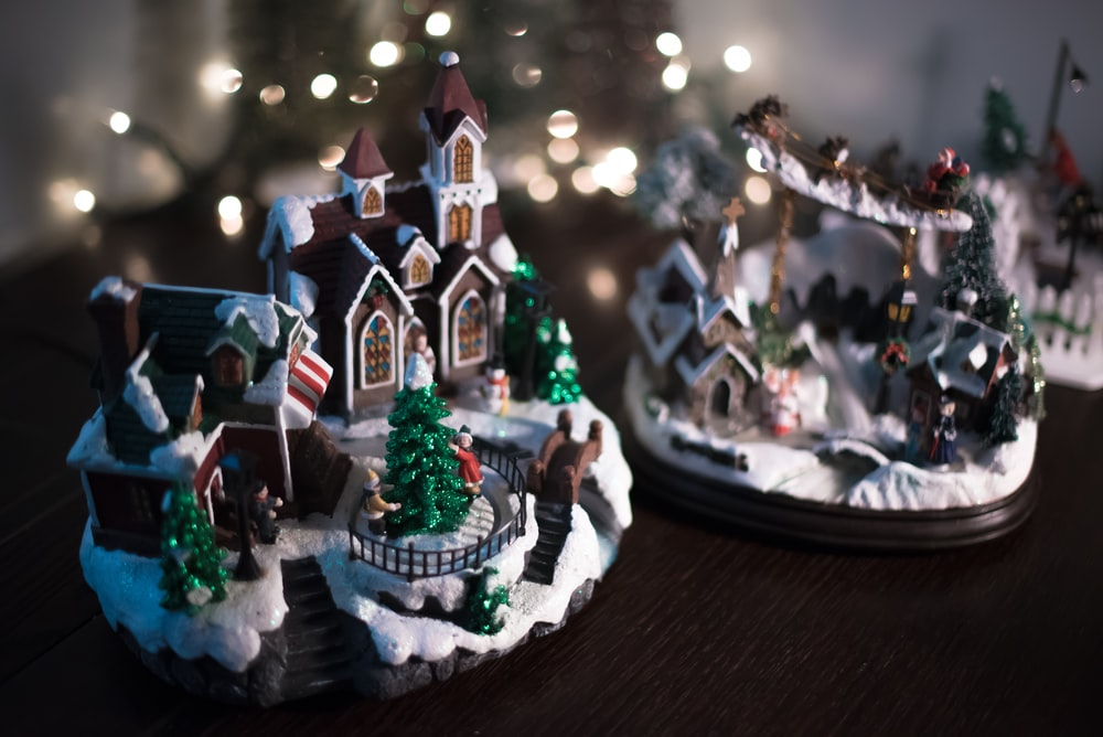 brown and white miniature house on brown wooden plank